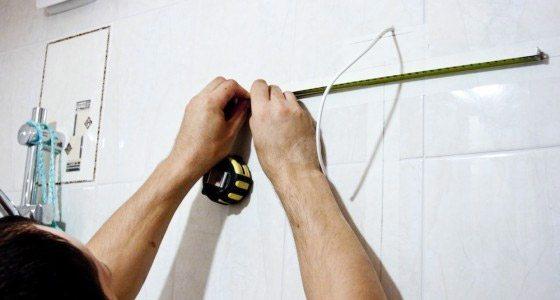Демонстрируется, как повесить шкаф на стену из пеноблоков.