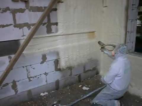 На фото – на стену наносят пенополиуретан