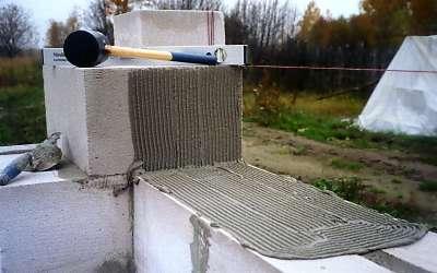 На фото – нанесение клея на блоки своими руками.