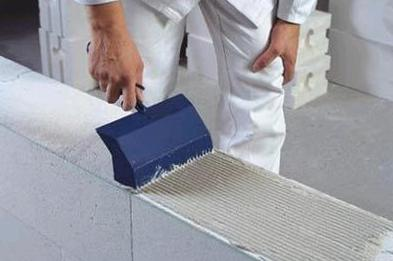 На фото – специальный зубчатый шпатель со стенками, которые не позволяют раствору выходить за границу пеноблоков