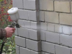Нанесение жидкого утеплителя на стену при помощи распылителя