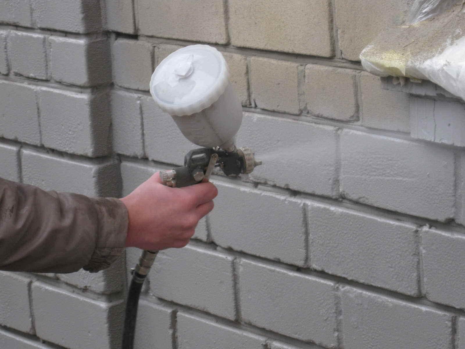 Нанесение жидкого утеплителя на стену
