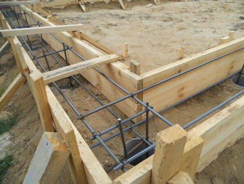Подготовленная траншея для заливки ленточного основания с учетом того, что держаться оно будет на бетонных сваях собственного производства
